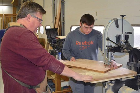 Instructor Kevin McKnight, left, watches as Ryan  Hughes cuts wood during carpentry class.