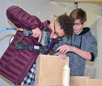 Raymon Rogers-Casando, left, and Logan Robinson work on a wood-working project during carpentry class at the Home Builders Association of Northern Kentucky.